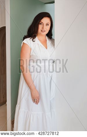 Attractive Woman In White Dress Stands In The Doorway