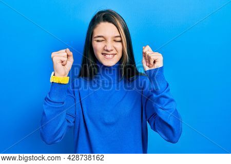 Young brunette girl wearing turtleneck sweater excited for success with arms raised and eyes closed celebrating victory smiling. winner concept.