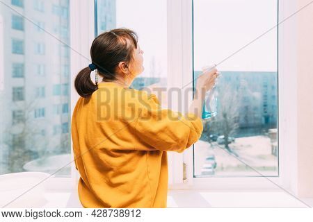 Woman Of Fifty In Yellow Sweater And Jeans Washes Dusty Window In Apartment. 50 Year Old Woman Clean