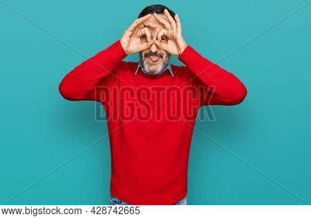 Middle age hispanic man wearing casual clothes doing ok gesture like binoculars sticking tongue out, eyes looking through fingers. crazy expression.