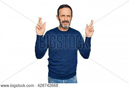 Middle age hispanic man wearing casual clothes gesturing finger crossed smiling with hope and eyes closed. luck and superstitious concept.