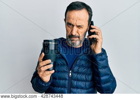 Middle age hispanic man talking on the smartphone and drinking a cup of coffee skeptic and nervous, frowning upset because of problem. negative person.