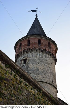 High Round Watchtower Of A Medieval Fortress Or Castle On A Blue Sky Background