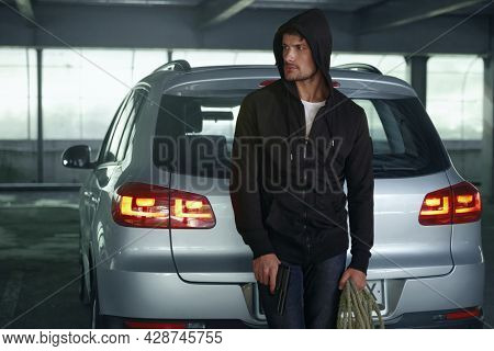Focused european robber standing near private automobile. Male bearded bandit wear black hoodie and hold pistol with rope. Concept of robbery and kidnapping. Inside parking lot