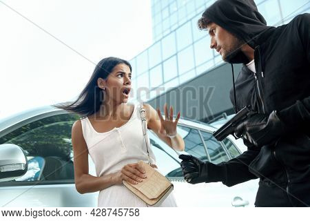 Angry robber want to steal handbag of frightened girl. Male bandit wear black hoodie and hold pistol. Young brunette woman standing near near her automobile. Concept of robbery. City daytime