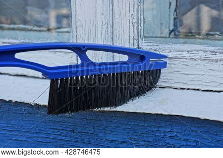 Plastic Blue Brush With Black Bristles Sweeps The Dust Off The White Windowsill On The Street