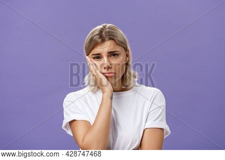 Waist-up Shot Of Unhappy Miserable And Sad Cute Blonde Female In White Casual T-shirt Pursing Lips L