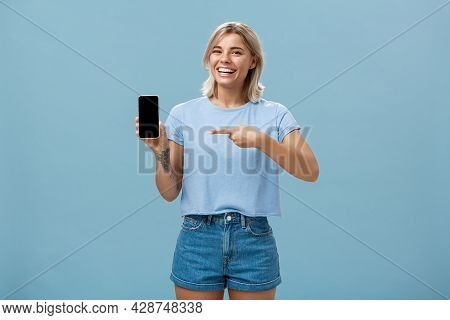 Look At This Hilarious Photo. Entertained Attractive Happy Woman With Fair Hair In Casual T-shirt An