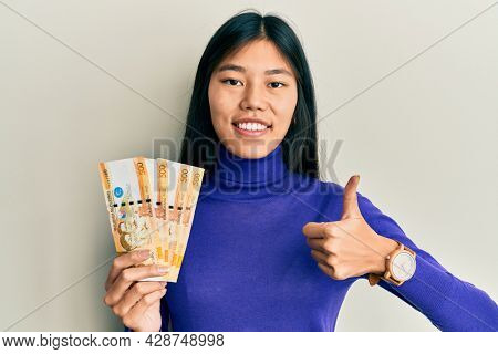 Young chinese woman holding 500 philippine peso banknotes smiling happy and positive, thumb up doing excellent and approval sign