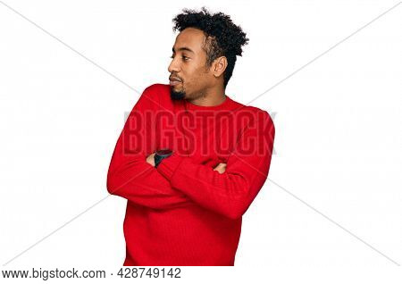 Young african american man with beard wearing casual winter sweater looking to the side with arms crossed convinced and confident