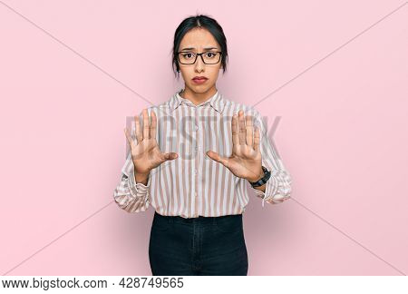 Young hispanic girl wearing casual clothes and glasses moving away hands palms showing refusal and denial with afraid and disgusting expression. stop and forbidden.