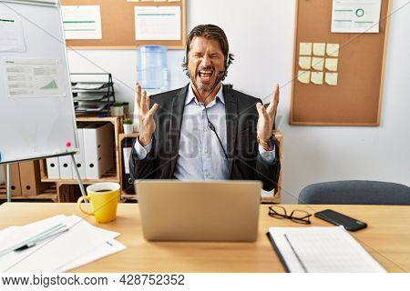 Handsome middle age man wearing call center agent headset at the office crazy and mad shouting and yelling with aggressive expression and arms raised. frustration concept.