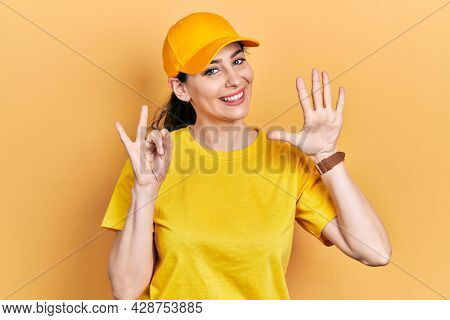 Young hispanic woman wearing delivery uniform and cap showing and pointing up with fingers number seven while smiling confident and happy.