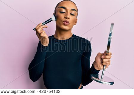 Hispanic man wearing make up and long hair holding mirror applying make up looking at the camera blowing a kiss being lovely and sexy. love expression.