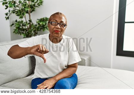 Mature hispanic woman sitting on the sofa at home looking unhappy and angry showing rejection and negative with thumbs down gesture. bad expression.