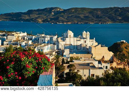 Picturesque scenic view of Greek town Plaka on Milos island over red geranium flowers. Plaka village, Milos island, Greece. Focus on flowers