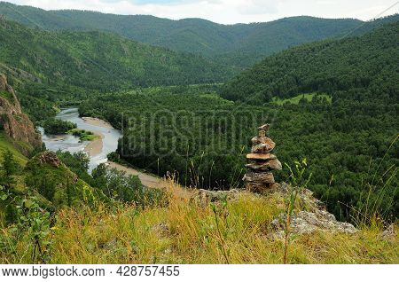 A Ritual Stone Pyramid On Top Of A Mountain Overlooking A Beautiful Winding River Flowing Through Th