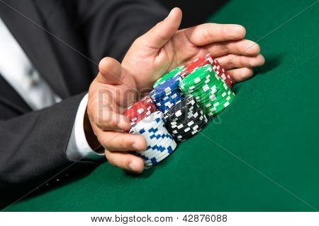 """Gambler stakes """"all in"""" pushing his chips forward. Risky entertainment of gambling"""