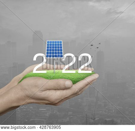 2022 White Text With Solar Cell On Green Grass Field In Man Hands Over Pollution City Tower And Skys