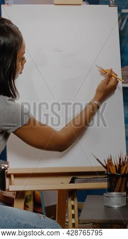 Artist Of African American Ethnicity Drawing Vase On White Canvas With Pencil And Craft Tools At Stu