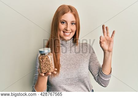 Young irish woman holding bowl with lentils doing ok sign with fingers, smiling friendly gesturing excellent symbol