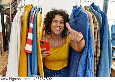 Young hispanic woman searching clothes on clothing rack using smartphone approving doing positive gesture with hand, thumbs up smiling and happy for success. winner gesture.