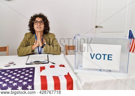 Young hispanic woman at political election sitting by ballot begging and praying with hands together with hope expression on face very emotional and worried. begging.