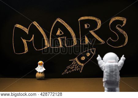 Figures Of Astronauts On The Background Of A Chalky Black Board With The Inscription Mars And A Flyi