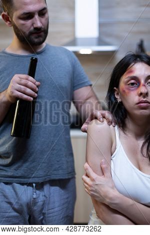 Alcoholic Husband Harassing Abused Wife With Bruises. Violent Man Holding Bottle Of Alcohol Threaten