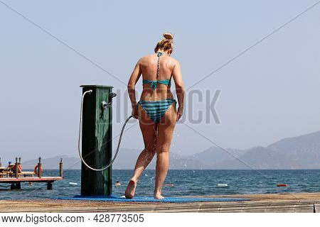 Shower On A Beach, Blonde Woman In Striped Bikini Washes Standing On Background Of Sea And Misty Mou