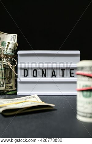 Lightbox Board With Word Donate In Black Letters Around Us Dollar Banknotes. Money, Business, Financ