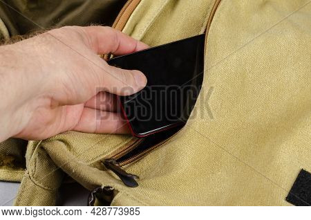 Close-up Of A Man's Hand Putting A Smartphone In The Pocket Of His Shoulder Bag. A Canvas Casual Bag