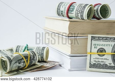 Knowledge Leads To Wealth. Stack Of Books With Dollars. Concept Of Expensive Education. Money In Boo