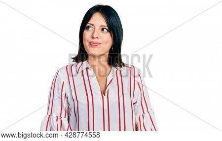Young hispanic girl wearing casual clothes smiling looking to the side and staring away thinking.