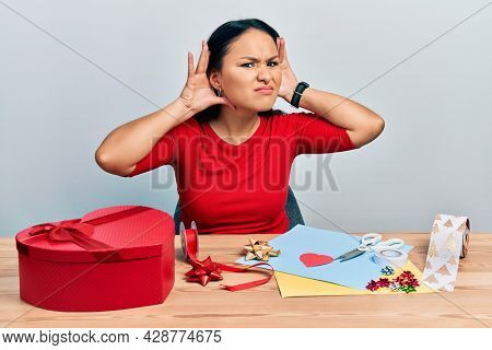 Beautiful hispanic woman with nose piercing doing handcraft creative decoration trying to hear both hands on ear gesture, curious for gossip. hearing problem, deaf