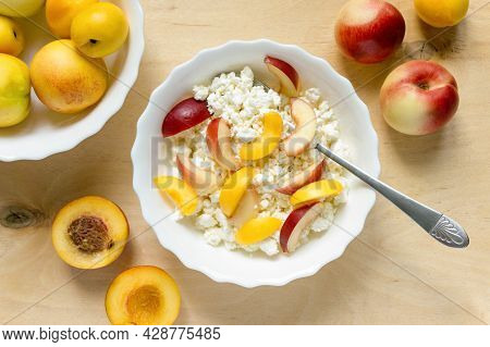 Cottage Cheese With Nectarine In White Bowl On Wooden Background, Top View