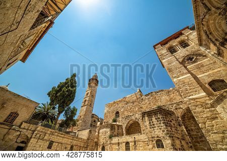 Exterior view of the Church of the Holy Sepulchre and minaret under blue sky in Old City of Jerusalem, Israel.