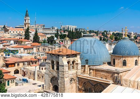 Cupola of the Church of the Holy Sepulchre among rooftops under blue sky in Old City of Jerusalem, Israel (view from above).