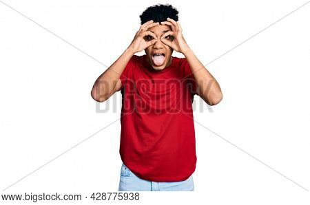 Young african american man wearing casual red t shirt doing ok gesture like binoculars sticking tongue out, eyes looking through fingers. crazy expression.