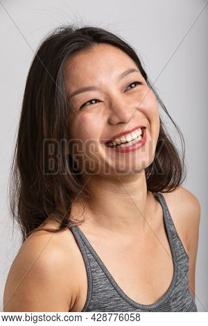 Portrait beautiful Asian girl with big smile and brown hair. Sportswear and lipstick. White background