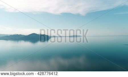 Mirrored Water Reflects Blue Sky With Mountain Horizon. Shot. Picturesque Landscape With Reflection
