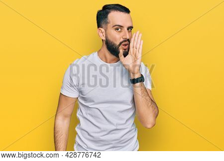 Young man with beard wearing casual white t shirt hand on mouth telling secret rumor, whispering malicious talk conversation