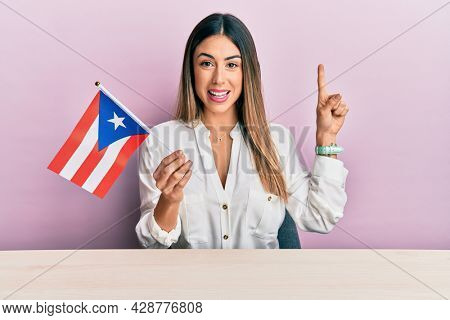 Young hispanic woman holding puerto rico flag sitting on the table smiling with an idea or question pointing finger with happy face, number one