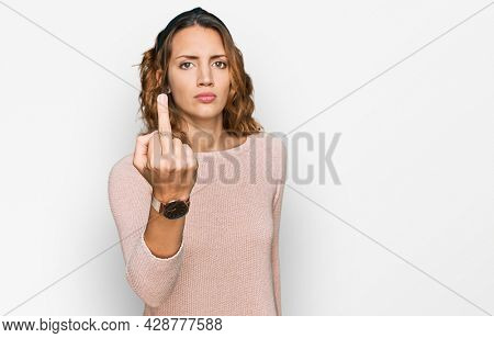 Beautiful young caucasian woman wearing casual sweater showing middle finger, impolite and rude fuck off expression