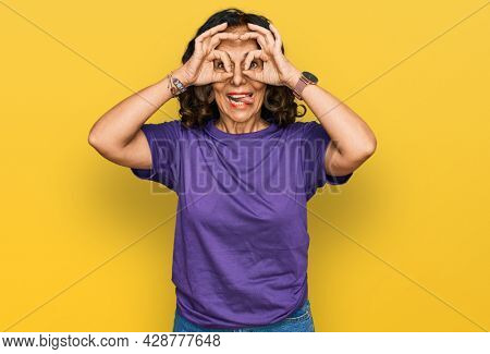 Middle age hispanic woman wearing casual clothes doing ok gesture like binoculars sticking tongue out, eyes looking through fingers. crazy expression.