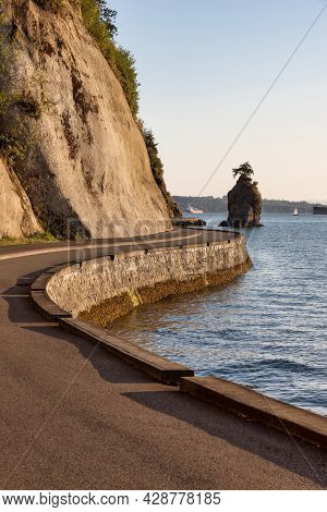 View Of The Siwash Rock From Seawall At Stanley Park In A Modern City. Downtown Vancouver, British C