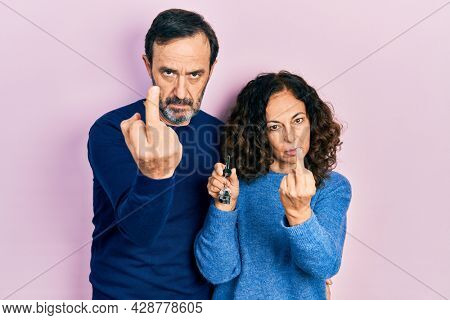 Middle age couple of hispanic woman and man holding keys of new home showing middle finger, impolite and rude fuck off expression