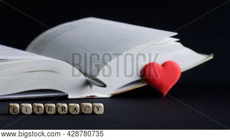 Lettering Literacy Next To An Open Book, Red Heart And Pen. The Concept Of Sympathy For Literacy And