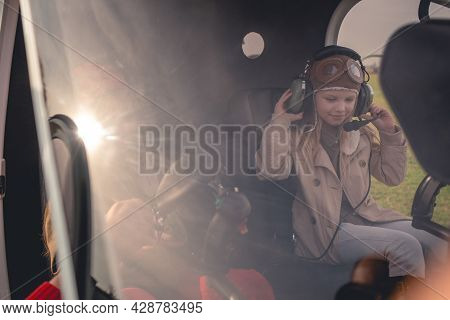 Tween Girl Putting On Headset On Pilot Seat In Helicopter