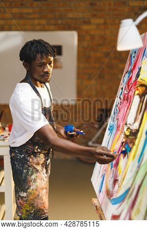 African american male painter at work painting on canvas in art studio. creation and inspiration at an artists painting studio.